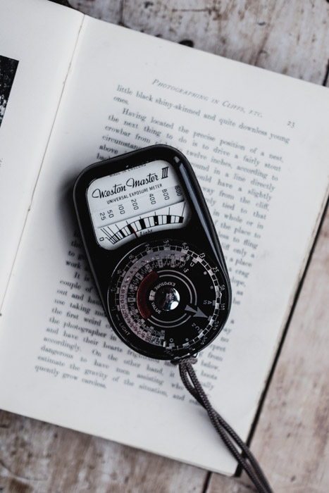 Photo of a handheld light meter on a book. Tips for Light Meter Photography