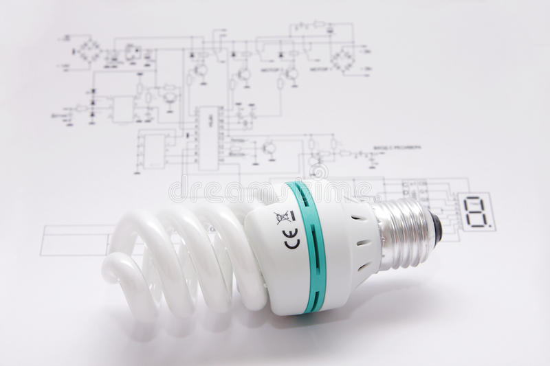 A better light bulb. The light bulb saving up energy lays on the electrotechnical scheme stock photo