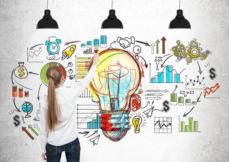 Blond woman drawing a light bulb, scheme. Rear view of a blond woman drawing a large and colorful light bulb and a business scheme on a concrete wall royalty free stock photography