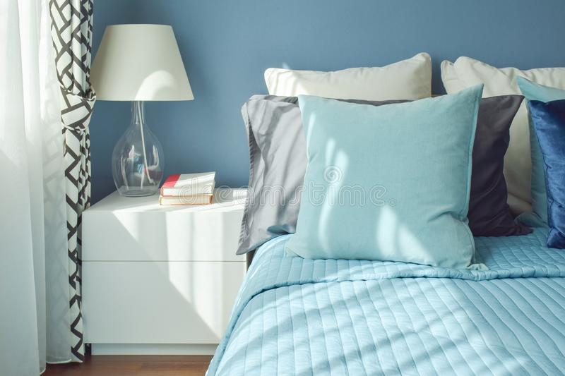 Blue color scheme bedding and white table lamp with natural light. From a window royalty free stock image