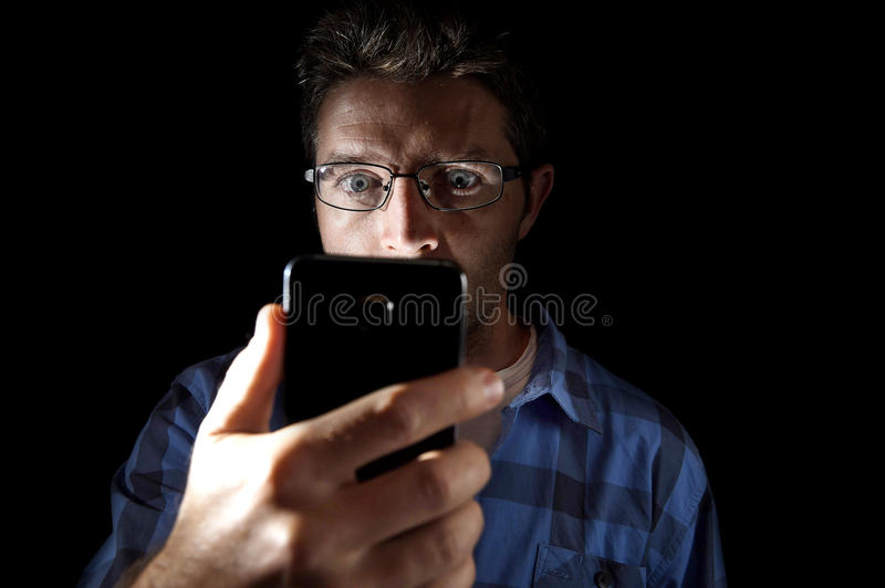 Close up portrait of young man looking intensively to mobile phone screen with blue eyes wide open isolated on black background. Close up portrait of young man stock photo