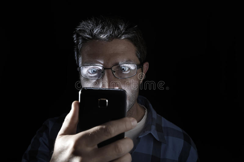 Close up portrait of young man looking intensively to mobile phone screen with blue eyes wide open isolated on black background. Close up portrait of young man stock images