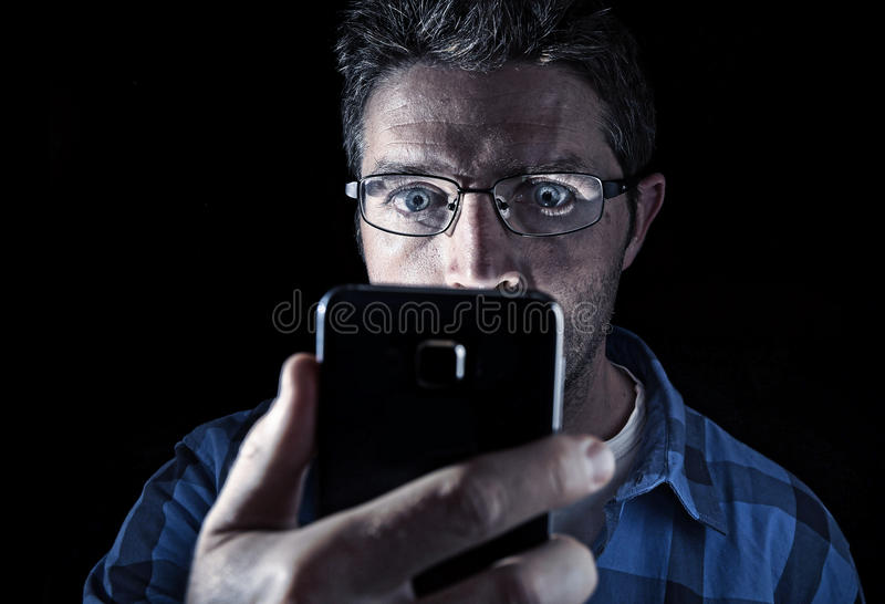 Close up portrait of young man looking intensively to mobile phone screen with blue eyes wide open isolated on black background. Close up portrait of young man stock photography