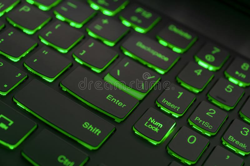 Colorful keyboard for gaming. Backlit keyboard with green color scheme. Colorful light keyboard.  stock photos