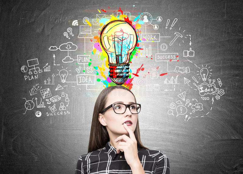 Geek girl in glasses with a light bulb, scheme. Portrait of a nerdy girl in glasses standing near a blackboard with a business scheme and a colorful light bulb royalty free stock image