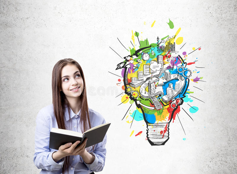 Happy college student, light bulb scheme. Young businesswoman in a blue shirt wearing a dark red lipstick is standing with an open book near a concrete wall stock image