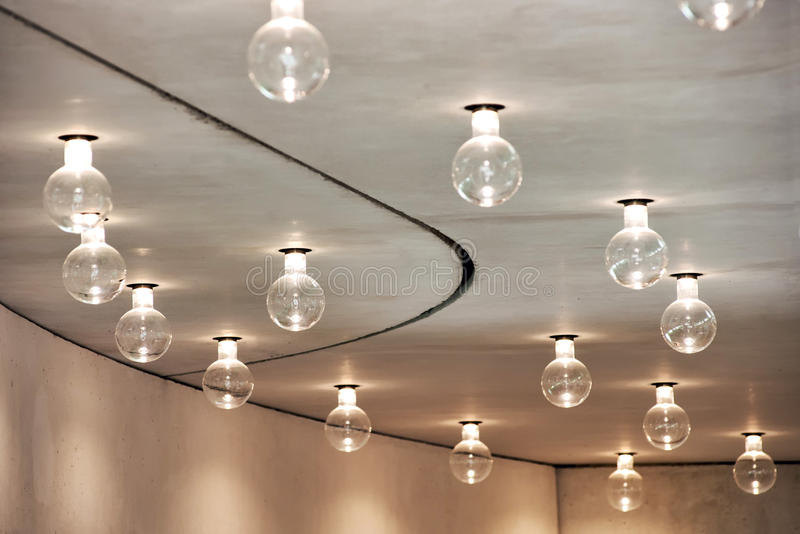 Lightbulbs Arranged in Pattern in Room Ceiling. Architectural Detail of Room Lighting Scheme - Close Up of Exposed Globe Light Bulbs Hanging in Pattern from royalty free stock photo