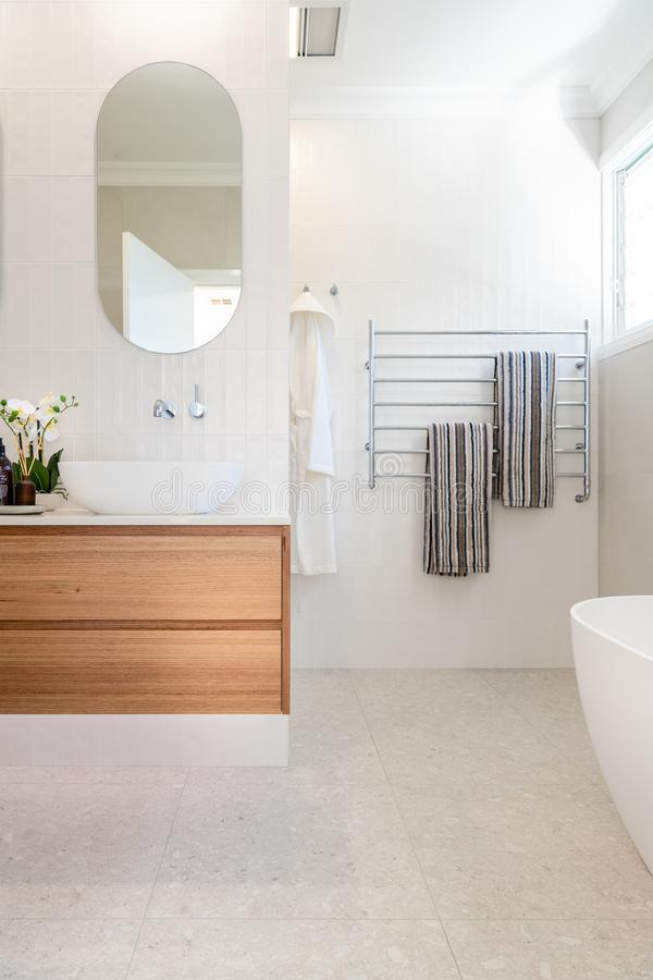 Luxury domestic bathroom shower and vanity with oak dresser drawers, white colour scheme. And bright lighting royalty free stock photography