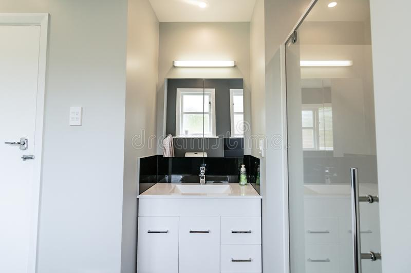Modern White Apartment Bathroom. Small city apartment interior with white basin, sink shower and lighting stock photography