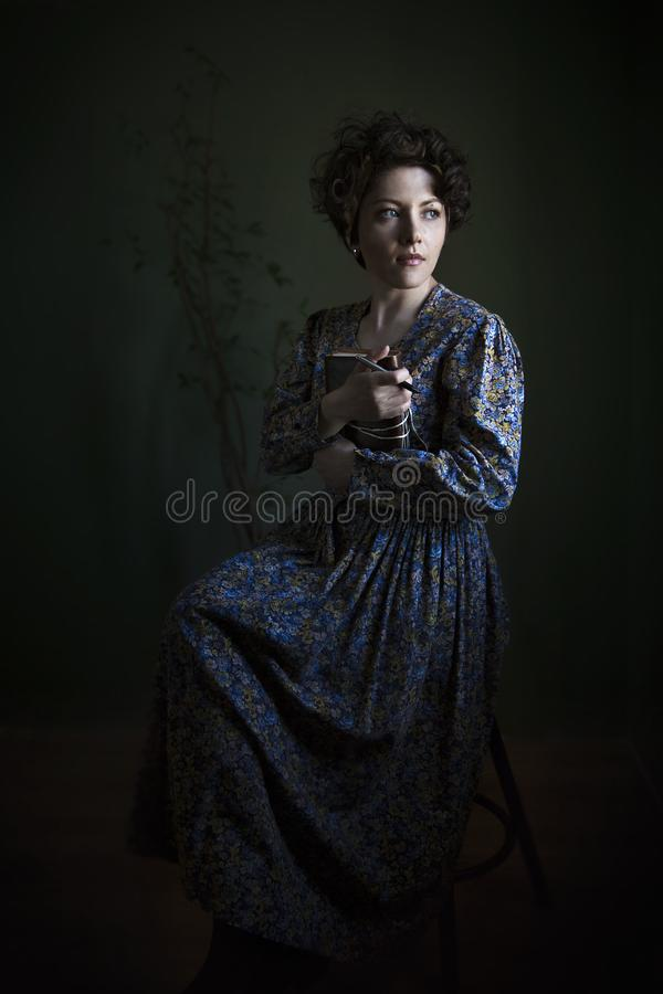 Portrait of a young woman in a beautiful English dress. The light scheme of Rembrandt, where the only light source - light from th. Portrait of a young woman in stock photography