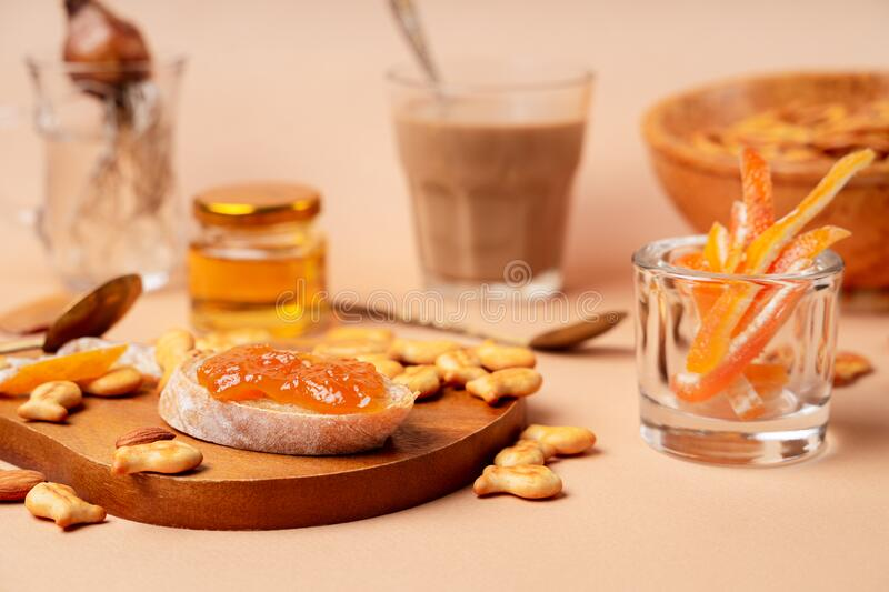Sweet breakfast with cappuccino in a glass. Beige and orange monochrome color scheme, closeup view. Horizontal orientation, biege, background, dessert, food stock images